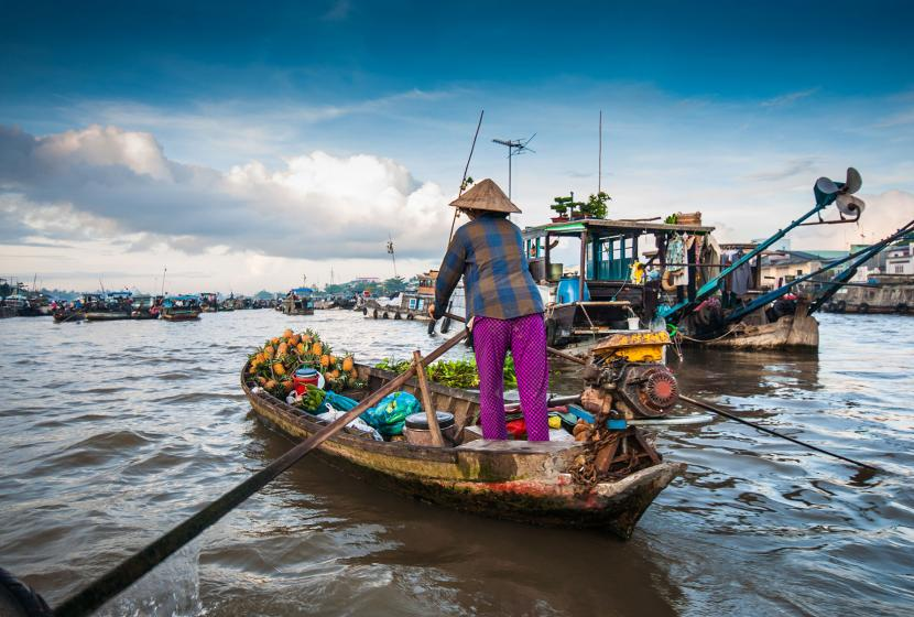 A vendor paddles through the Mekong River to sell goods at the floating market