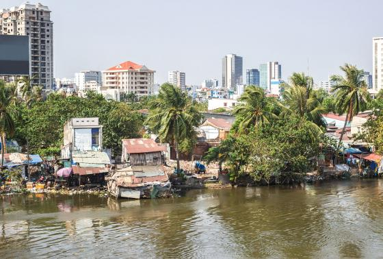 Poor houses along the river in Ho Chi Minh City, Vietnam with skyscrapers in the distance