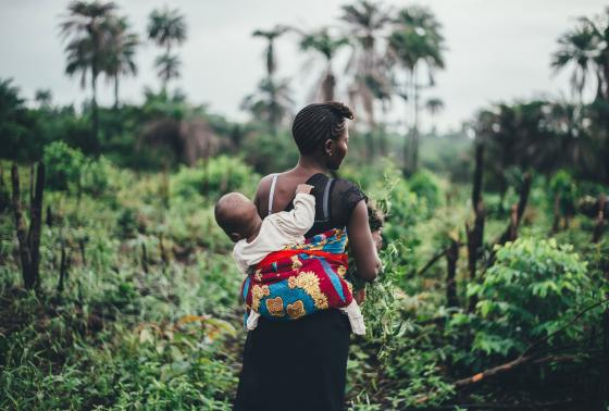 A woman works in a field while carrying her baby on her back.